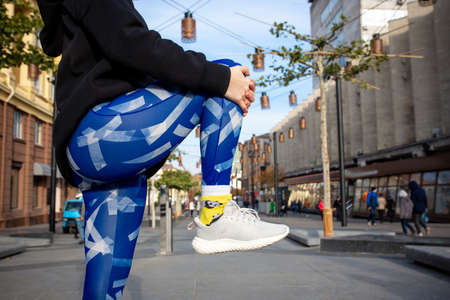 Crop portrait of young sport woman in blue leggings and black sweatshirt doing fitness exercise in the street. Outdoor sports clothing and shoes, urban style. Healthy lifestyle and sport concept.