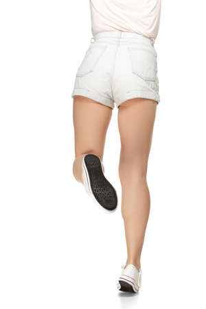 Back view of slender female legs in stylish sport shoes over white background.