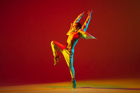 Young male dancer dancing hip-hop isolated over red background in neon light
