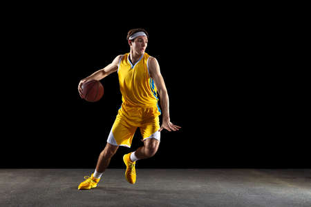 Young Caucasian basketball player training isolated on black background.