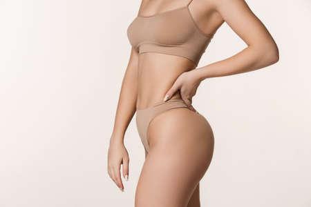 Close-up slim tanned female body in underwear over white background. Banco de Imagens