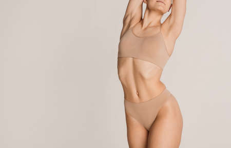 Beautiful female body in color underwear over grey background.