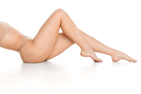 Beautiful slender tanned female legs in underwear over white background. Stock Photo