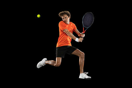 Young Caucasian man, tennis player training isolated on black background.