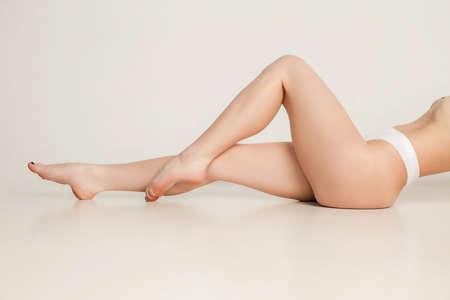 Beautiful slender tanned female legs in underwear over white background.
