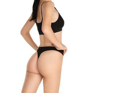 Rear view of slender female body in black underwear over white background.