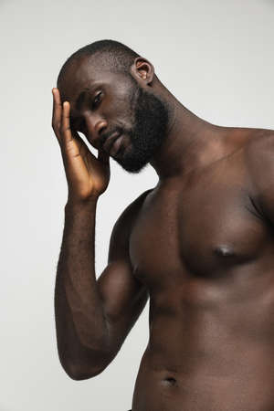 Half-length portrait of young handsome muscled African man posing isolated over white background. Archivio Fotografico