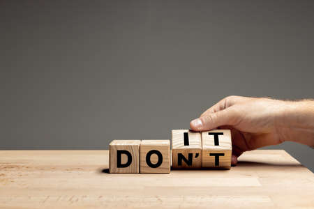 Male hand flips wooden cubes with words DO IT to DONT on the table over grey background. Copyspace for ad.