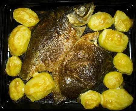 Baked fish with potatoes on a baking sheet Stock Photo - 9572392