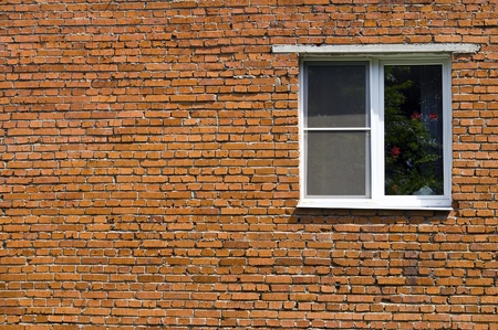 window at the brick wall of the house photo