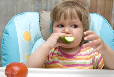 The kid is bite off a cucumber