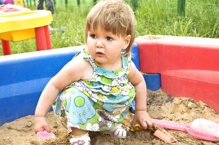 小さな女の子が、サンド ボックスで遊んで