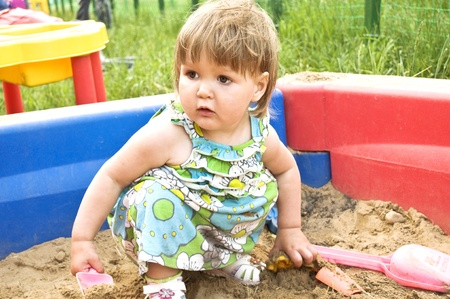 Little girl playing in the sandbox