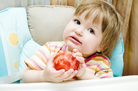Little girl holding a tomato and smiling Stock Photo - 10562267