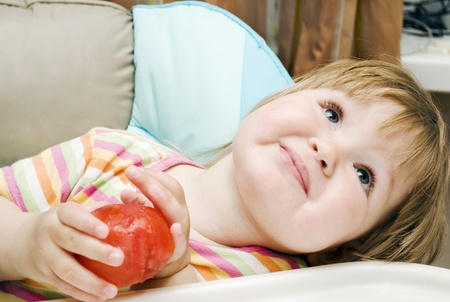 Little girl holding a tomato and smiling Stock Photo - 10562203