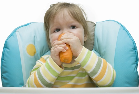 The kid eats carrots on a white background Stock Photo - 10861727