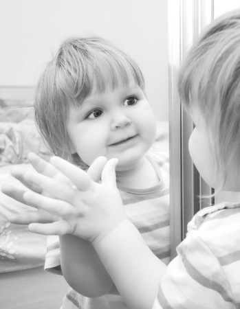 A girl looks in the mirror. Black and White image of baby. Stock Photo