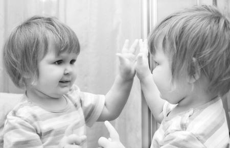 spiegels: Een meisje kijkt in de spiegel. Zwart-wit beeld van de baby.