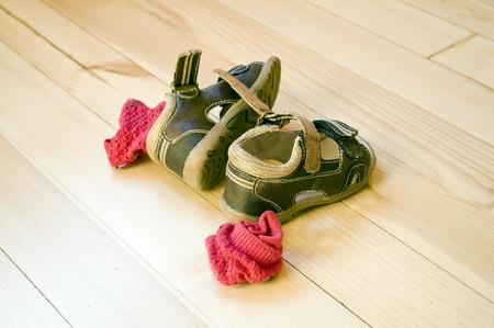 Childrens sandals on wooden floor photo
