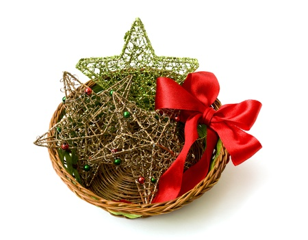 Christmas decorations: stars and red bow in a wicker vase Stock Photo