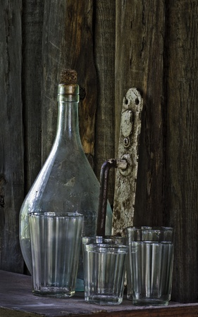 Still life - old bottle, glass, doorhandle, balance on wooden background  photo