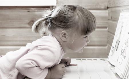 Baby girl sitting with opened book  Standard-Bild