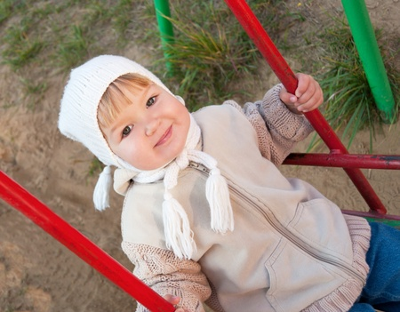 Smiling child on swing in park  photo