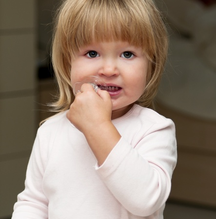 Little girl chewing on pacifier photo