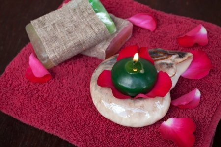Red rose petals, candle, soap and towel  photo