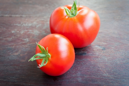 Two red fresh tomatoes on a wooden table.  Stock Photo - 15092578