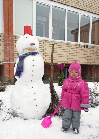 Little girl and a snowman in the yard photo