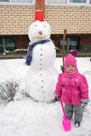 baby girl with a shovel and a snowman in the yard photo
