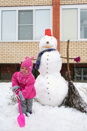 Little girl with a shovel and a snowman in the yard photo