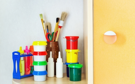 Tools of the artist: paints, brushes on a shelf in the children's room   photo