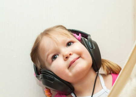 Cute baby with headphones looking at camera. Little beautiful girl in headphones listens to music photo