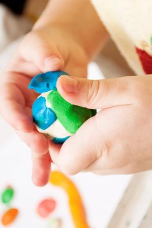 子は、テーブル上の粘土から金型します。塑像用粘土の手.小さな女の子はカラフルな遊び、生地を使用して学んでいます。