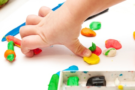 nurser: Child moulds from plasticine on table. hands with plasticine. Little girl is learning to use colorful plasticine