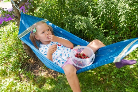 Little girl lying on hammock, eating berries and dreams Stock Photo