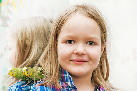 to remain dormant: little girl with wavy parrot on his shoulder Stock Photo