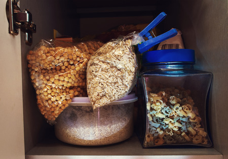 wild oats: Open kitchen cabinet. Cereals on the kitchen shelf. Stock Photo
