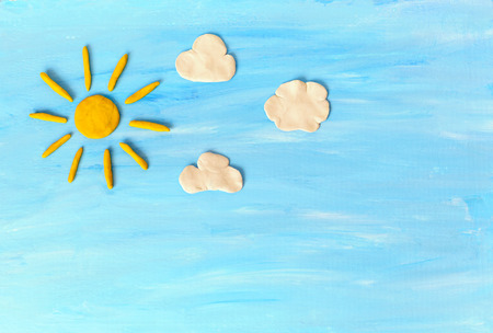Sun clouds on blue sky. Made from modeling clay Stock Photo