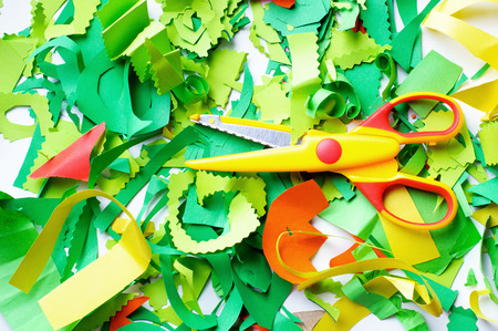 cut: Pieces of colored paper and yellow scissors. Pieces of colored paper that sliced child