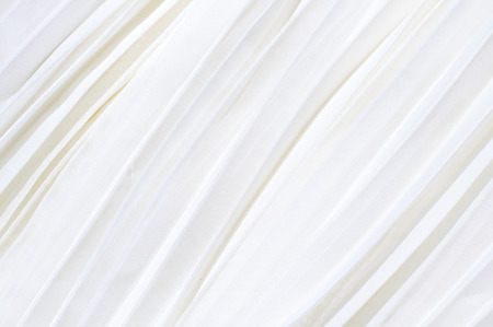 Background of white pleated fabric located diagonally