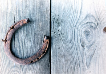 western culture: Old rusty horseshoe on vintage wooden board- rustic scene in a country style. Old iron Horseshoe - good luck symbol and mascot of well-being in a village house in Western culture.