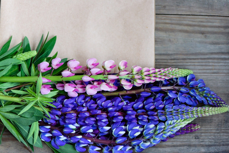 Purple and blue beautiful lupines petal and flowers on wooden background