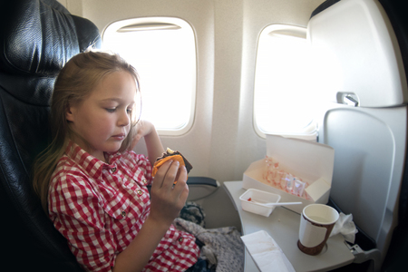 windows: Cute young girl having a meal in the airplane while flying.