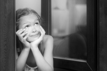 windows: dreaming cute little girl by the window. Black and white photo.