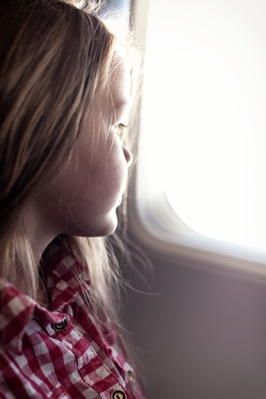 windows: Adorable little girl traveling by an airplane. Child sitting by aircraft window and looking outside. Stock Photo