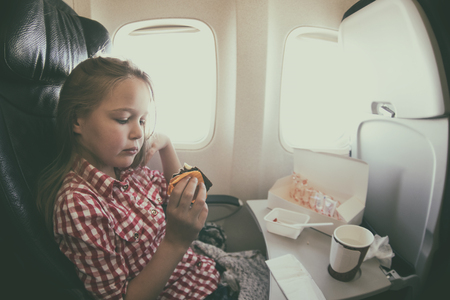 windows: Cute young girl having a meal in the airplane while flying. Toned photo