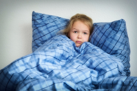 Sad adorable little girl in the bed closeup and looking at the camera. Banco de Imagens